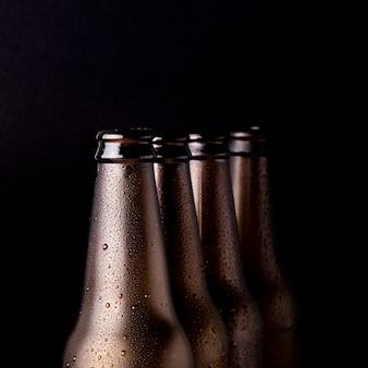 Linea di bottiglie di birra nere
