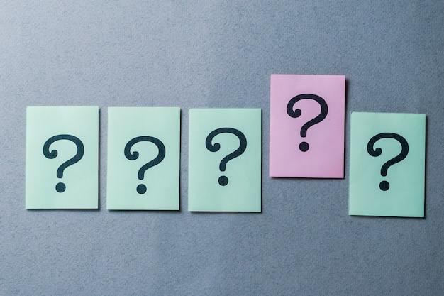 Linea di cinque punti interrogativi stampati su grigio