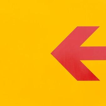 Linea di freccia rossa minimalista su sfondo giallo
