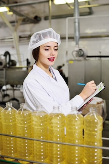 Linea di produzione alimentare di raffinato olio di girasole. lavoratrice in una fabbrica su una superficie di trasporto con bottiglie di olio vegetale.