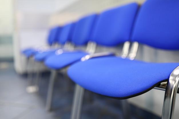 Linea di sedie blu vuote per visitatori alla reception o in banca