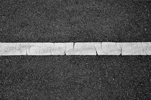 Linea di verniciatura bianca su asfalto nero. sfondo del trasporto spaziale