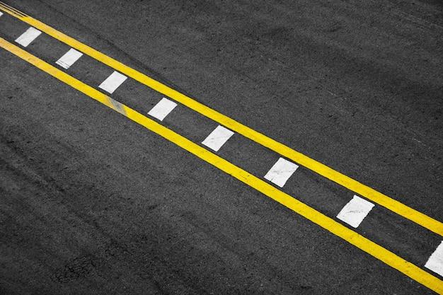 Linea di verniciatura gialla e bianca su asfalto nero. sfondo del trasporto spaziale