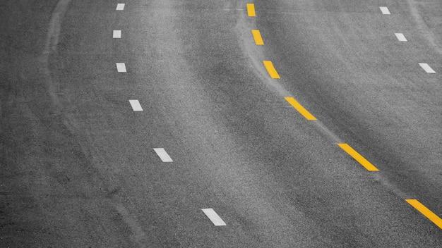 Linea di verniciatura gialla e bianca su asfalto nero