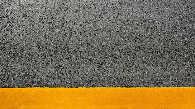 Linea di verniciatura gialla su asfalto nero. sfondo del trasporto spaziale