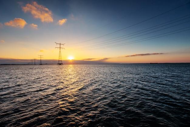 Linea elettrica sopra l'acqua durante un tramonto fantastico