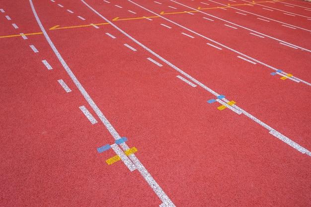 Linee bianche di stadio e struttura di piste da corsa in gomma rossa da corsa
