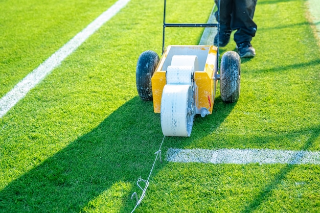 Linee bianche disegnate sul campo di calcio con vernice bianca sull'erba usando una macchina speciale prima di una partita