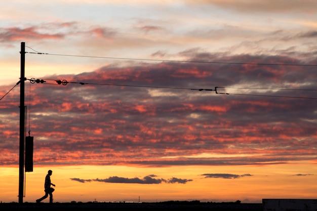 Linee di filo della ferrovia contro un cielo nuvoloso alla fine della giornata.
