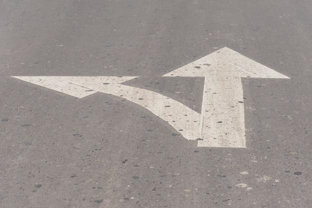 Linee di freccia bivio su asfalto