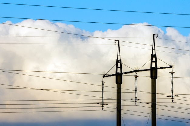 Linee elettriche di trasmissione di elettricità contro le nuvole bianche. torri ad alta tensione