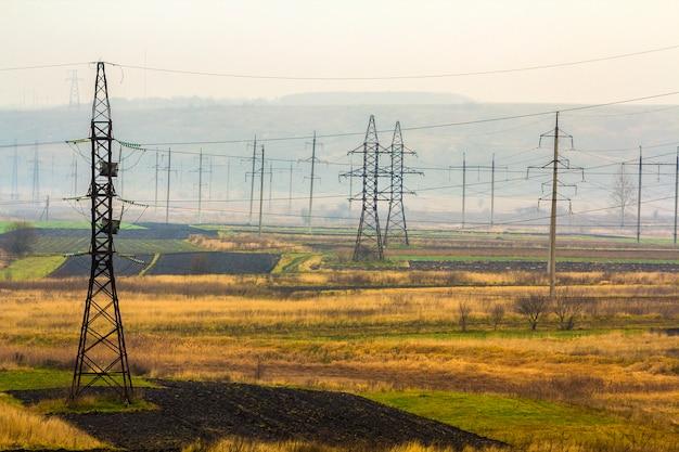 Linee elettriche di trasmissione di elettricità in tempo nebbioso. torri ad alta tensione
