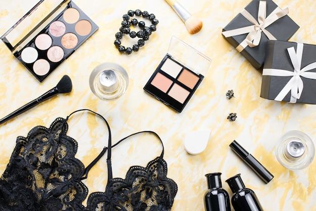 Lingerie di pizzo nero con prodotti di bellezza, cosmetici da trucco, gioielli in nero e oro. moda piatto laico, vista dall'alto