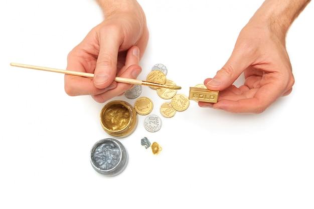 Lingotti. mani di uomini, monete d'oro e d'argento, pennello, barattoli di vernice