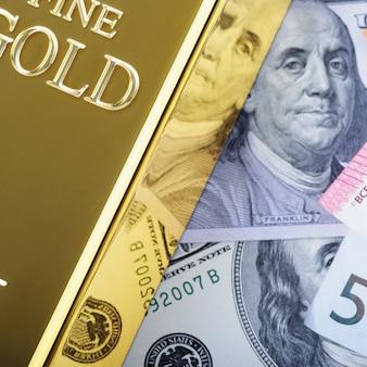 Lingotto di lingotti di metallo oro sullo sfondo del dollaro e fatture in euro.
