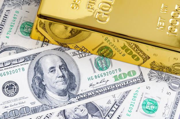 Lingotto di lingotti di metallo oro sullo sfondo delle banconote da un dollaro.