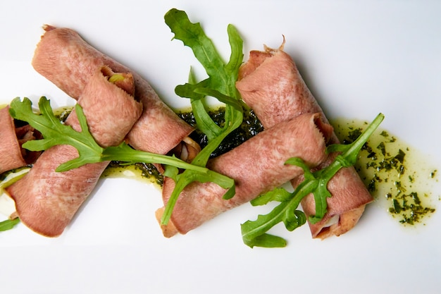 Lingua cotta con ripieno e salsa su un piatto bianco.