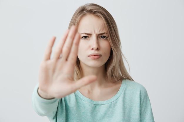 Linguaggio del corpo. disgustata stressata arrabbiata bionda giovane femmina con i capelli lisci in posa contro il muro, tenendo la mano nel gesto di arresto, cercando di difendersi come se stesse dicendo: stai lontano da