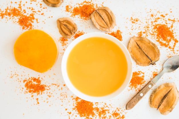 Liquido arancione tra fogliame e pepe