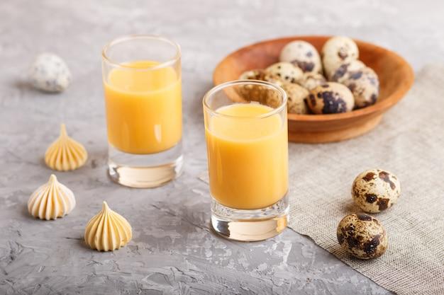 Liquore all'uovo dolce in vetro con uova di quaglia e meringhe su cemento grigio. vista laterale