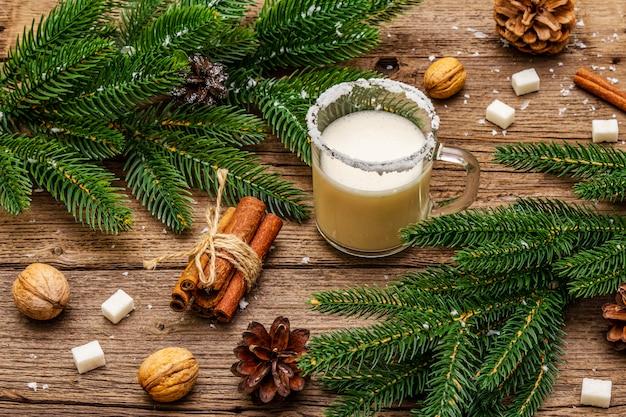 Liquore allo zabaione natalizio o cola de mono cocktail. classica bevanda invernale in tazza di vetro, decorazioni natalizie. rami sempreverdi, cannella, noci, zucchero.