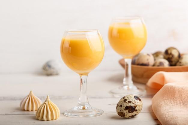 Liquore dolce dell'uovo in vetro con le uova e le meringhe di quaglia su di legno bianco. vista laterale, da vicino.