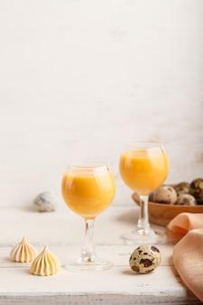 Liquore dolce dell'uovo in vetro con le uova e le meringhe di quaglia su fondo di legno bianco. vista laterale, copia spazio, verticale.