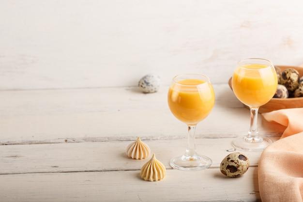 Liquore dolce dell'uovo in vetro con le uova e le meringhe di quaglia su fondo di legno bianco. vista laterale, copia spazio.