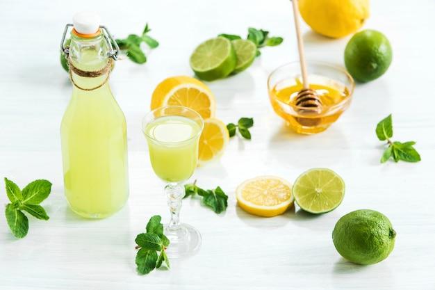 Liquore domestico della calce in un vetro e limoni e limette freschi su bianco