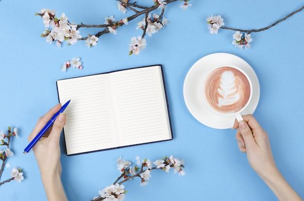 Lista dei desideri per i piani futuri. composizione piatta con fiori, blocco note e caffè