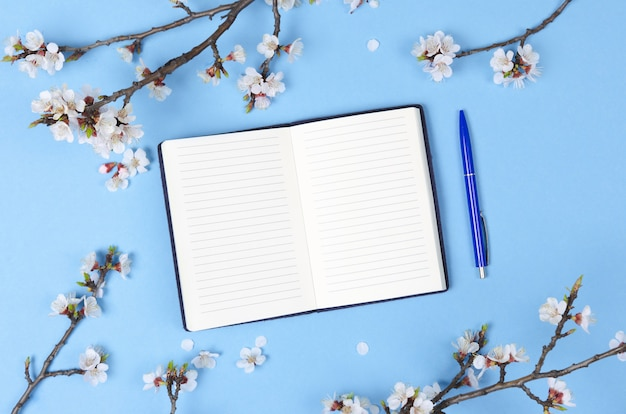 Lista dei desideri per i piani futuri. composizione piatta con fiori, blocco note