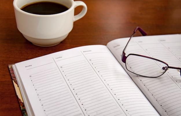 Lista di controllo in bianco sul tavolo di legno con caffè e bicchieri