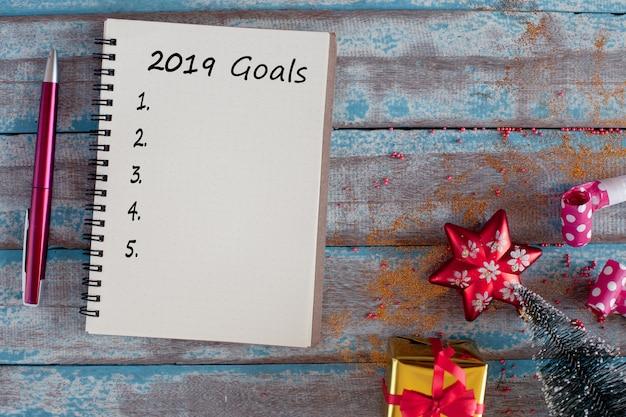 Lista di obiettivi 2019 con il taccuino e penna sulla tavola di legno blu rustica