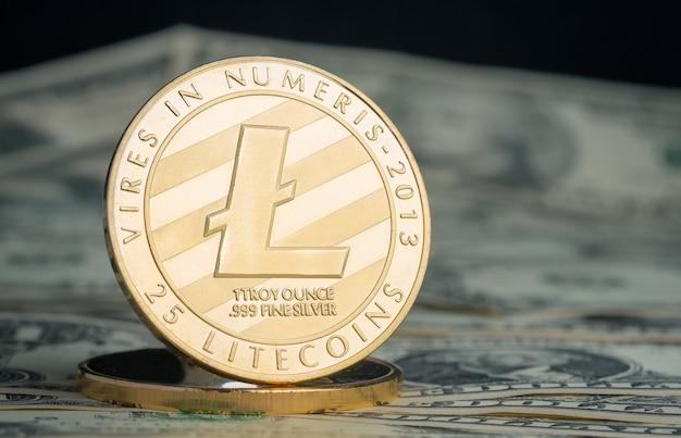 Litecoin di oro di valuta cripto sul fondo della banconota del dollaro.