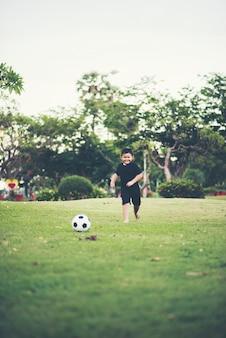 Little boy che gioca a calcio di calcio