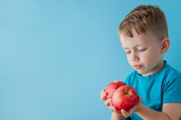 Little boy che tiene le mele in sue mani su fondo, sulla dieta e sull'esercizio blu per il concetto di buona salute