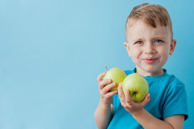 Little boy che tiene le mele nelle sue mani, dieta ed esercizio fisico per il concetto di buona salute