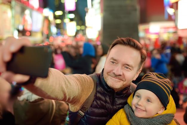 Little boy e suo padre prendendo selfie su times square a sera, nel centro di manhattan.