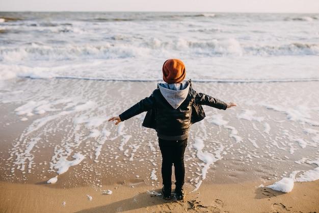 Little boy guardando le onde provenienti da una spiaggia