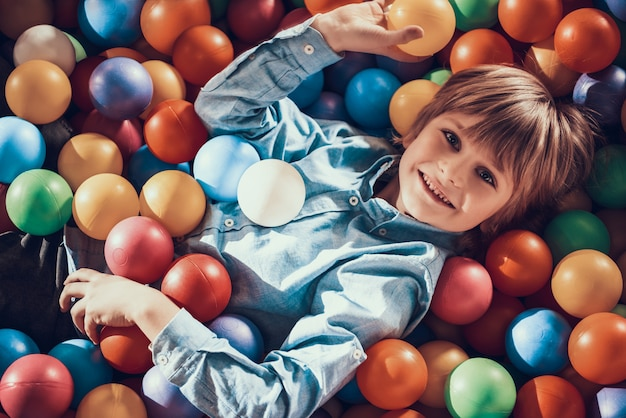 Little boy lying in pool pieno di palline colorate