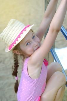 Little gir in cappello di paglia giocando al parco giochi.