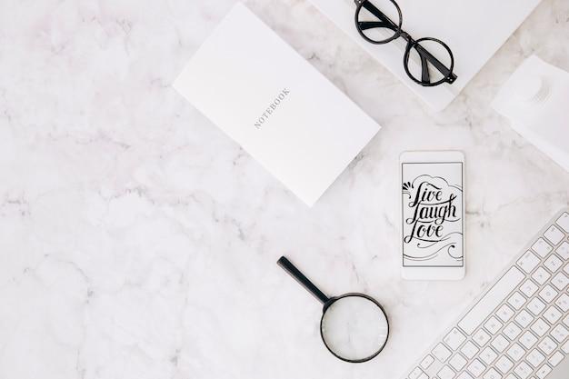 Live laugh love message sullo schermo mobile; taccuino; lente d'ingrandimento; occhiali da vista; cartone di latte e tastiera su sfondo con texture di marmo