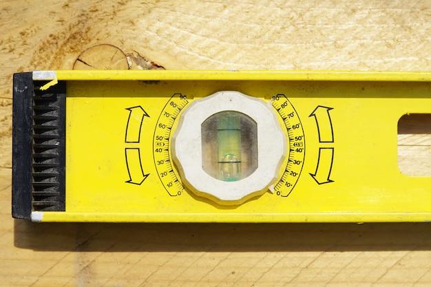 Livello di edificio giallo. strumento di lavoro su fondo in legno