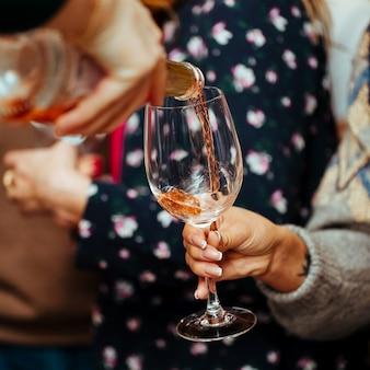 Lo champagne rosa viene versato in un bicchiere al visitatore.