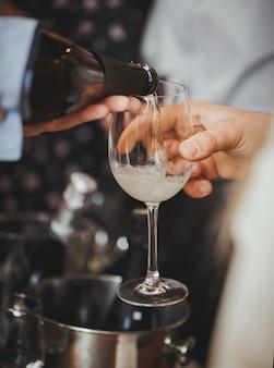 Lo champagne viene versato in un bicchiere al visitatore. avvicinamento.