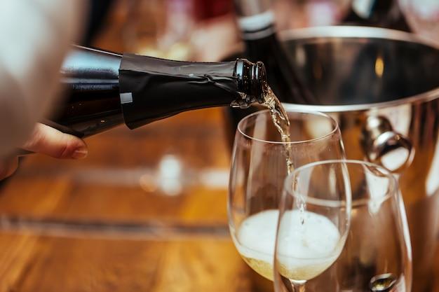 Lo champagne viene versato in un bicchiere sul tavolo. avvicinamento.