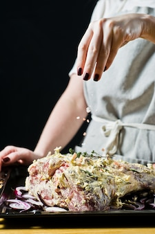 Lo chef cosparge il cosciotto di agnello crudo.
