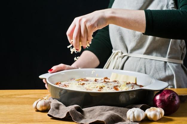 Lo chef cosparge le lasagne fatte in casa con parmigiano