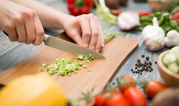 Lo chef di cucina taglia gli alimenti tagliati prepara le verdure