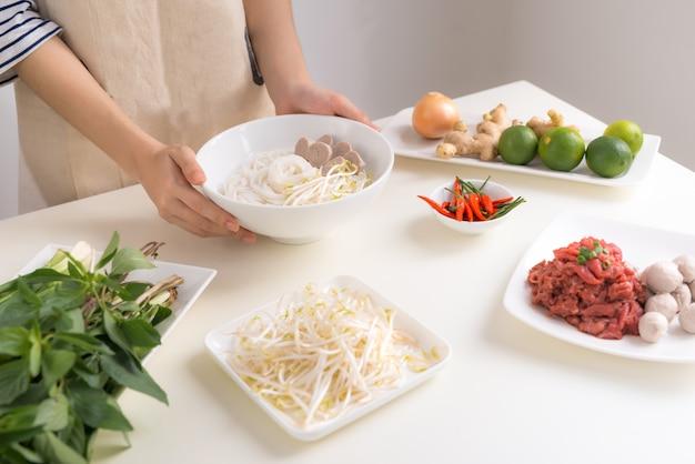 Lo chef femminile prepara la zuppa vietnamita tradizionale pho bo con erbe, carne, spaghetti di riso